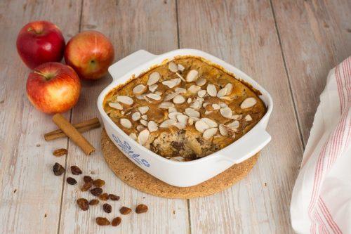 Apfel-Grieß-Auflauf ohne Zucker in einer weißen Auflaufform, daneben liegen Rosinen, Äfpeln und Zimstangen als Dekoration