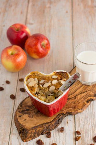 Apfel-Grieß-Auflauf ohne Zucker in einer roten Herz-Auflaufform, mit einem Löffel, Rosinen, Äpfeln und einem Glas Milch als Dekoration