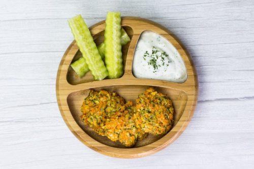 Zucchini-Puffer mit Süßkartoffel für Babys, auf einem Holzteller, mit Kräuterquark-Dip und Gurke